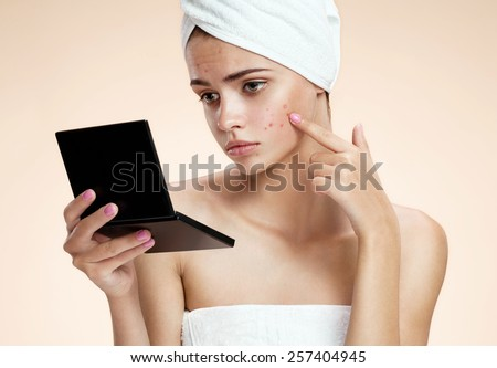 Teenager checking her face for pimple looking in the mirror. Woman with skin blemish looking at mirror isolated, beige background  - stock photo