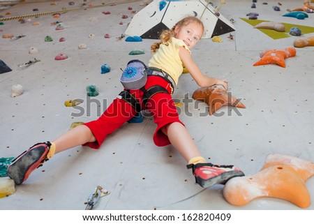 teenager climbing a rock wall - stock photo