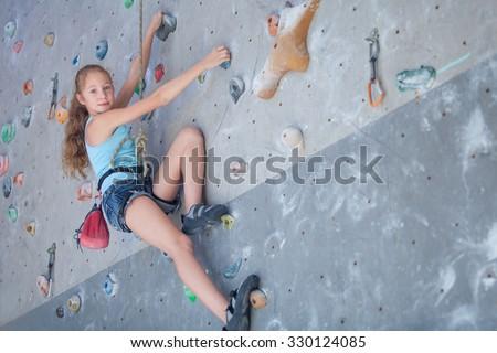 teenager climbing a rock wall indoor - stock photo