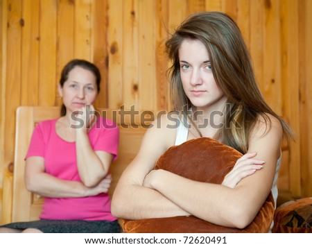 teenager daughter and mother after quarrel at home - stock photo