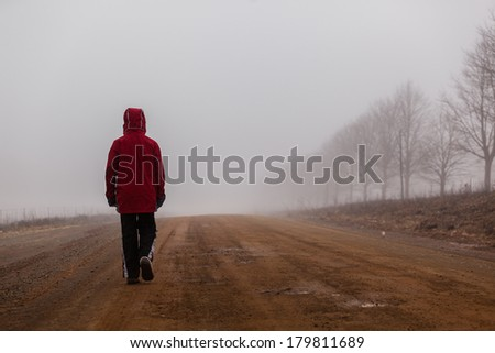 Teenager Dirt Road Mist Walking Teenager unidentified walking down mountain dirt road alone covered in cloud winter mist with color contrasts - stock photo
