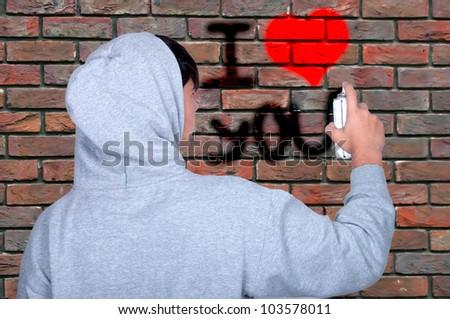 Teenager draws on a wall graffiti - stock photo
