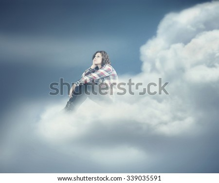 Teenager dreaming while she is sitting on a cloud.