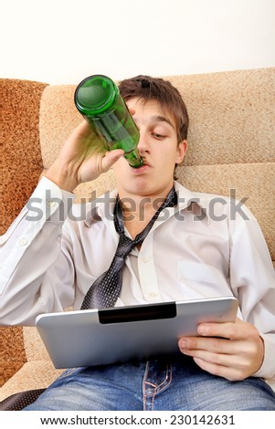 Teenager drinks a Beer with Tablet Computer on the Sofa at the Home - stock photo