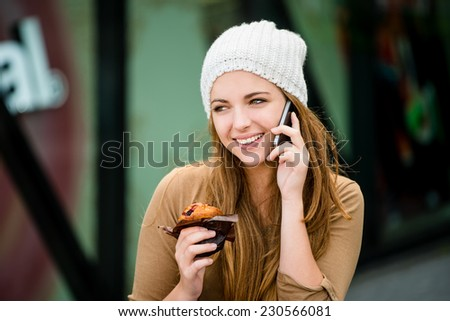 Teenager eating muffin in street and browsing internet on phone - stock photo