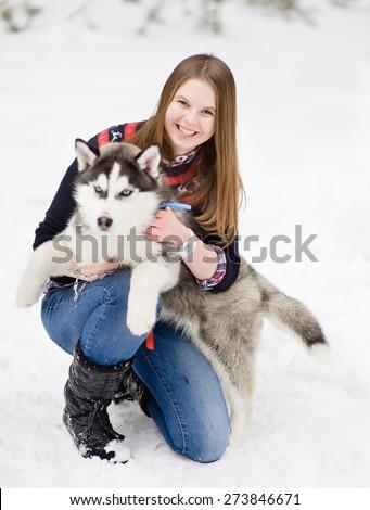 Teenager embracing hasky dog on snow - stock photo