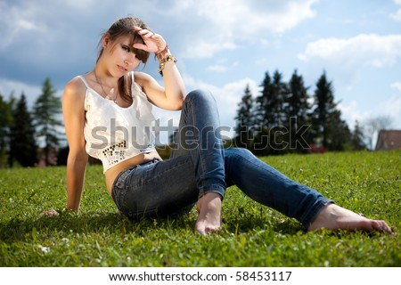 Teenager enjoying good weather outside during a summer day in the park. - stock photo
