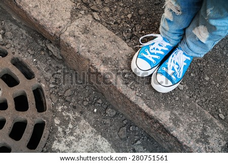 Teenager feet in jeans and blue shoes stand on the street edge. Photo with selective focus and shallow DOF - stock photo