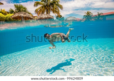 teenager floatsunder water in pool - stock photo