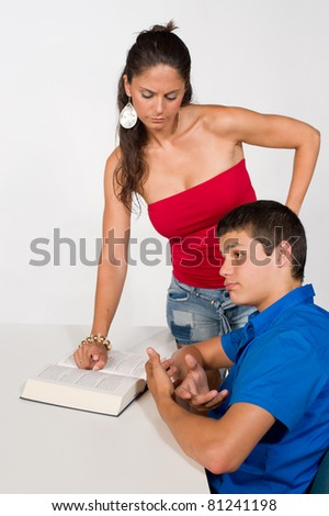 Teenager getting help with his homework, not very happy about it - stock photo