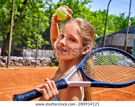 Teenager girl athlete holding  racket and ball on  brown tennis court. - stock photo