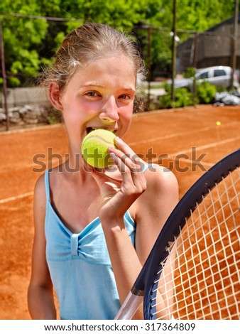 Teenager girl athlete  with racket and ball on  brown tennis court. - stock photo