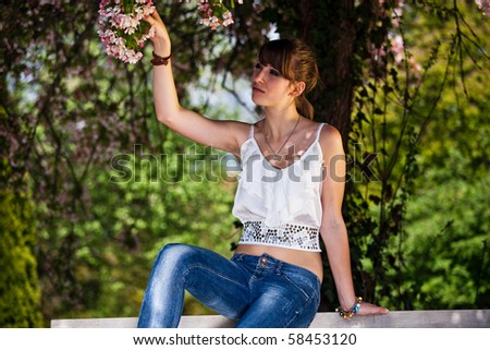 Teenager girl collecting flowers outside during a summer day in the park. - stock photo