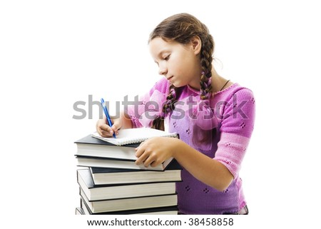 Teenager girl do homework,writing in textbook, on pile of books with concentration look,isolated on white - stock photo