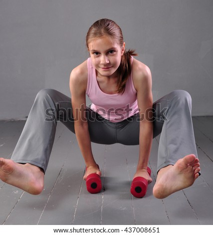 Teenager girl doing exercises with dumbbells to develop with dumbbells muscles on grey background. Sport healthy lifestyle concept. Full length portrait of teen child exercising with weights. - stock photo