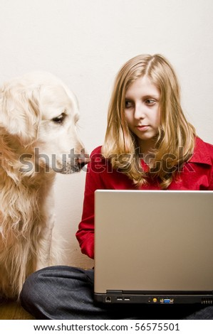 teenager girl doing her homework on a laptop with her dog beside - stock photo