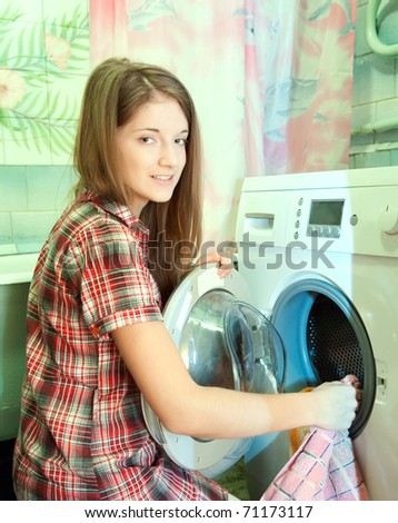 Teenager girl doing laundry at her home - stock photo