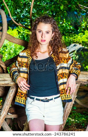 Teenager Girl. Dressing in black top, patterned fashion jacket, short pants, chunky chain bracelet, a teenager girl with curly long hair is standing in wooden area, waiting for you. Woman Fashion. - stock photo