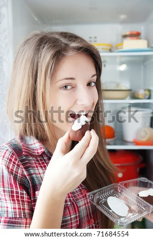 Teenager girl eating  pastry from  fridge  at home - stock photo