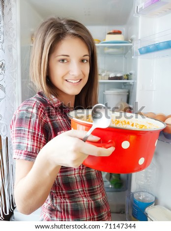 Teenager girl eating  soup from pan near fridge  at home