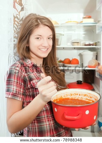 Teenager girl eating  soup from pan near fridge  at home - stock photo