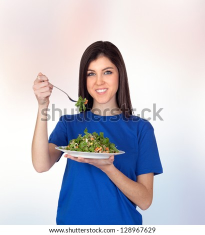 Teenager girl eating vegetables isolated on orange background - stock photo