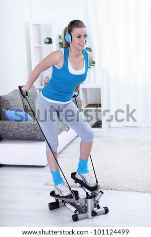 Teenager girl exercising on stepper trainer - stock photo