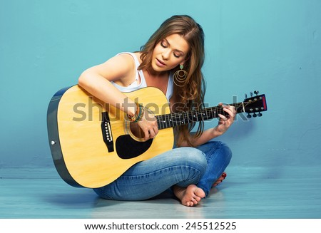 teenager girl guitar play . young model with long hair sitting on a floor. - stock photo