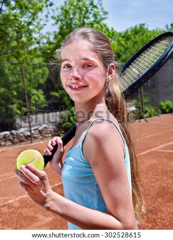 Teenager girl holding  racket and ball on  brown tennis court. - stock photo