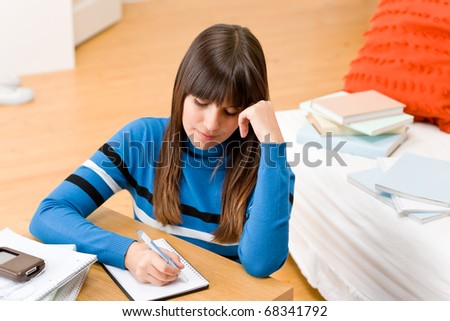 Teenager girl home - student write homework sitting at table - stock photo