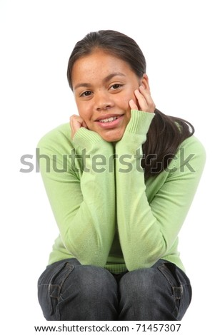 Teenager girl in studio elbows on knees relaxed - stock photo