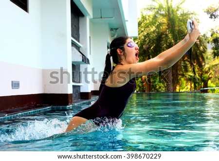 teenager girl  in swimming suit jump in water in swimming pool with camera in protective waterproof slipcover cover for underwater photo shooting footage - stock photo