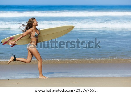 Teenager girl in swimsuit running fast along the beach holding her surfboard, hot surfer girl running to waves with her surfboard, beautiful young woman in bikini with surfboard run ready to surfing - stock photo
