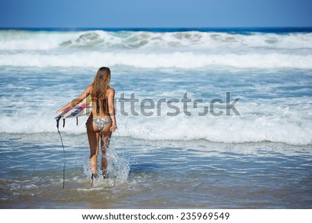 Teenager girl in swimsuit running fast to ocean waves holding her surfboard, hot surfer girl running to waves with her surfboard, beautiful young woman in bikini with surfboard run ready to surfing - stock photo