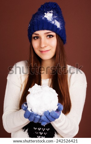 Teenager girl is holding snowball - stock photo