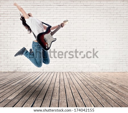 teenager girl jumping with electric guitar on a room - stock photo