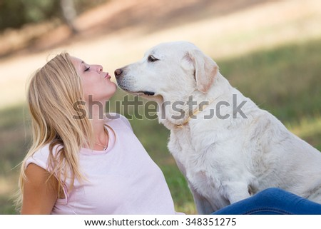 teenager girl kissing her very old senior labrador dog in the park, selective focus