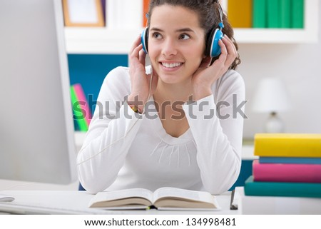 teenager girl listening music while sitting at a desk - stock photo