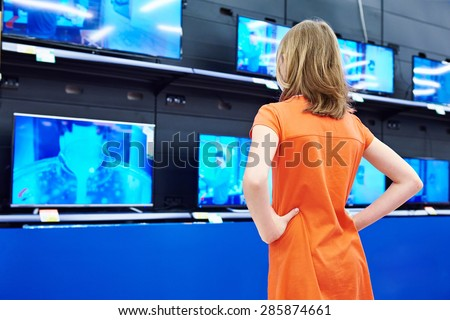 Teenager girl looks at LCD TVs in supermarket - stock photo