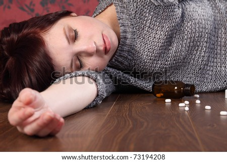 Teenager girl lying on the floor at home after an overdose of pills. Her eyes are closed and there is a bottle of pills on the floor beside her. - stock photo
