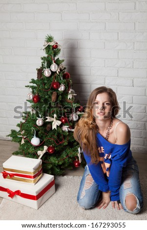 Teenager girl near christmas tree and fancy box - stock photo