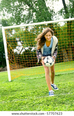 Teenager girl playing soccer and having the ball