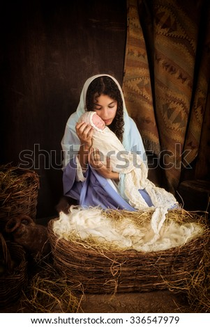Teenager girl playing the role of the Virgin Mary with a doll in a live Christmas nativity scene  (baby is a doll) - stock photo