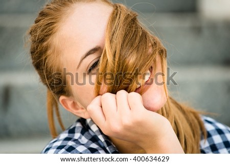 Teenager girl playing with her hair - outdoor on street - stock photo