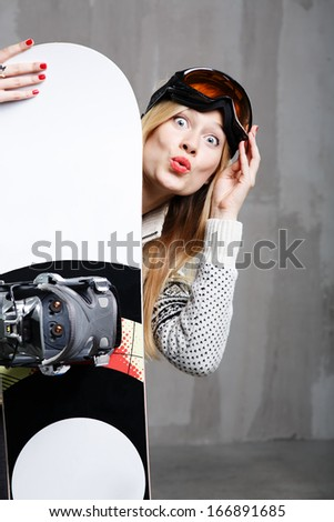 Teenager girl posing in the studio against concrete wall with snowboard - stock photo