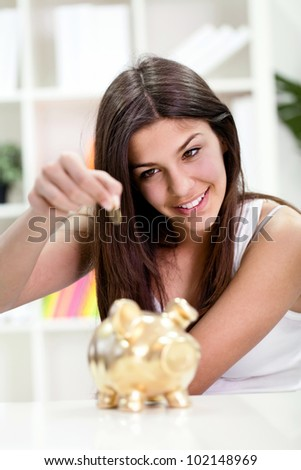 Teenager girl putting coin in golden piggybank banking, investment, - stock photo