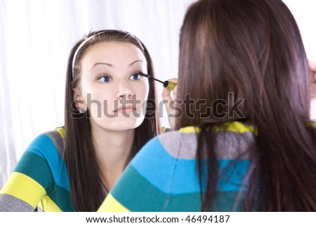 Teenager Girl Putting on Make Up in Front of a Mirror - stock photo