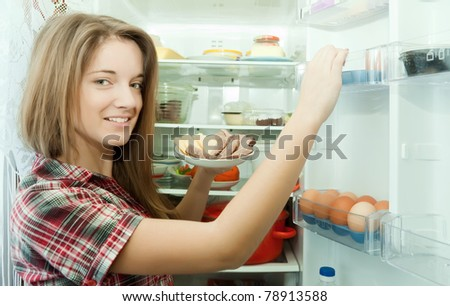Teenager girl putting snack into fridge  at home - stock photo