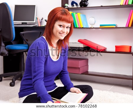 teenager girl reading book on floor in room - stock photo