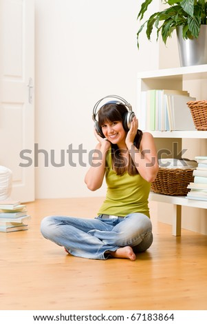 Teenager girl relax home - happy listen to music with headphones - stock photo